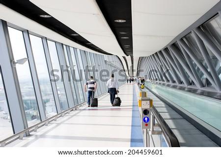 GATWICK, UK - JUNE 22. People walk toward the gate at Gatwick airport, England on June 22, 2014.  - stock photo