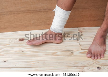 Gauze bandage of physician the treating case with ankle Injured on wooden floor background - stock photo