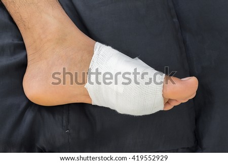Gauze bandage the foot,treating patients with foot ulcers,male is wrapping his Foot injury with bandage.( select focus Gauze bandage) - stock photo