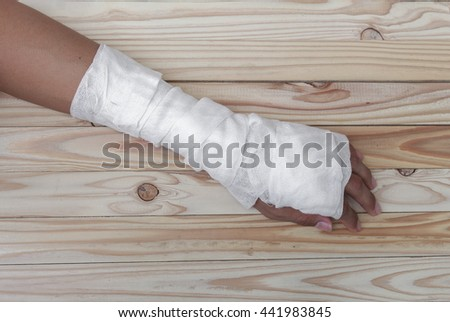 gauze bandage the hand contusion treating patients with hand  a wrist left  wrapping his injury on  wooden table background