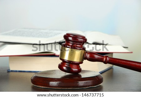 Gavel and books on table on light background