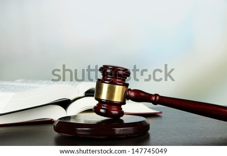 Gavel and books on table on light background - stock photo