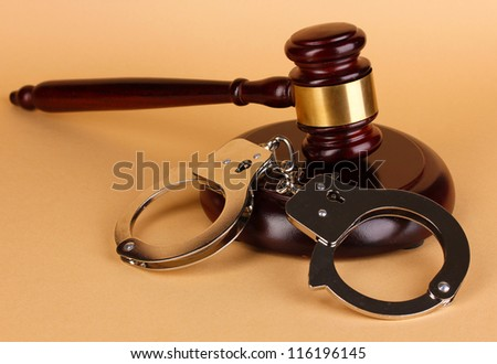 Gavel and handcuffs on beige background - stock photo