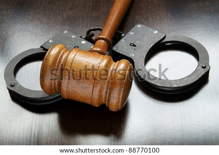 Gavel and handcuffs on wooden background - stock photo