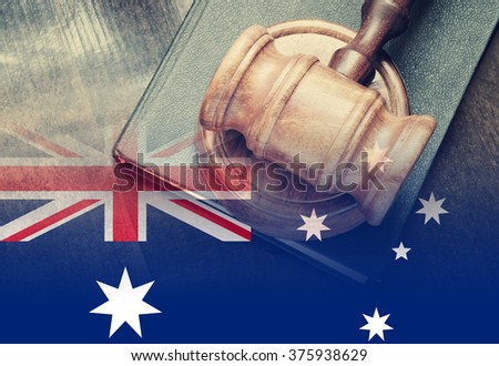 Gavel and legal book on wooden table, collage with flag of australia - stock photo