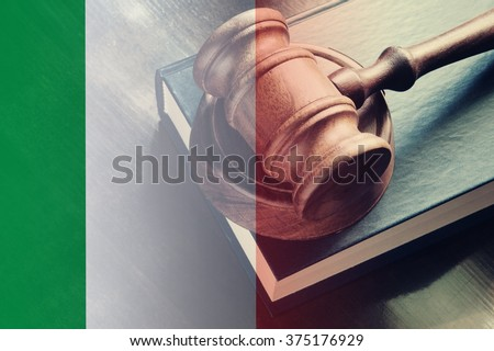 Gavel and legal book on wooden table, collage with flag of italy - stock photo