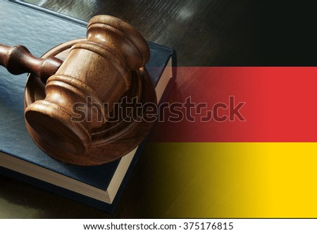Gavel and legal book on wooden table, collage with german flag - stock photo