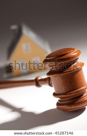 Gavel and Model Home on Gradated Background with Selective Focus. - stock photo