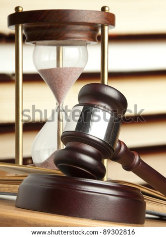 Gavel and old hourglass - stock photo