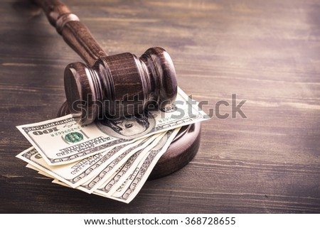 Gavel and some dollars banknotes on wooden table.Auction bidding, judicial system corruption concept.Toned - stock photo