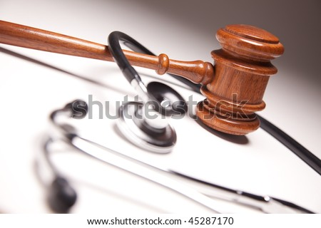 Gavel and Stethoscope on Gradated Background with Selective Focus. - stock photo