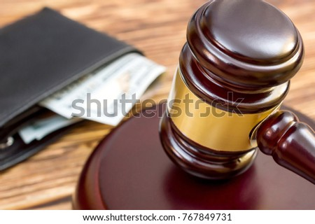 Gavel and wallet with money on the table. Close up.