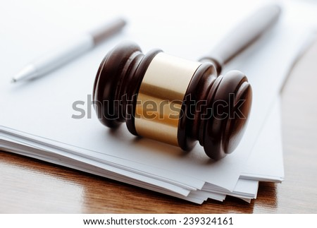Gavel, ball pen and paper for notes lie on the wooden desk. - stock photo