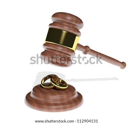 Gavel coming down on wedding rings - stock photo