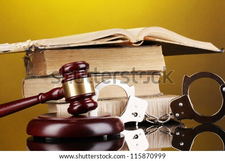 Gavel, handcuffs and book on law on yellow background