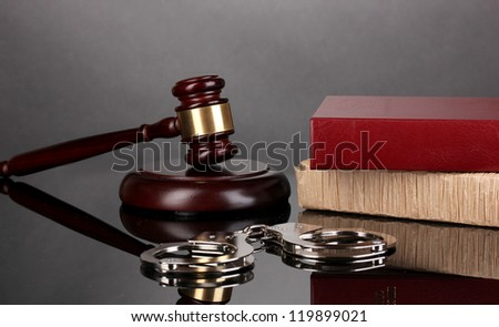 Gavel, handcuffs and books on law isolated on black - stock photo