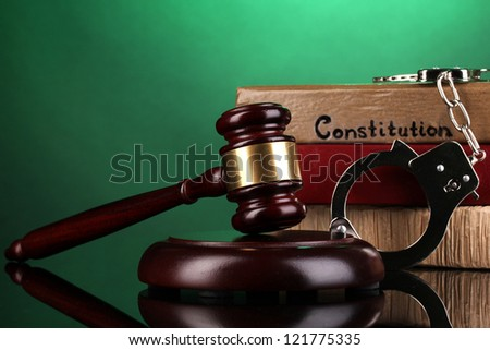 Gavel, handcuffs and books on law on green background