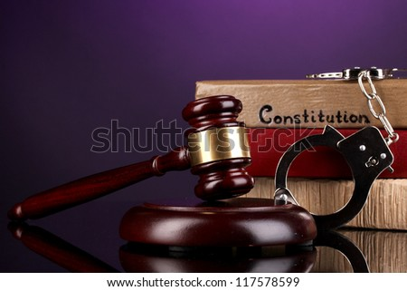 Gavel, handcuffs and books on law on purple background