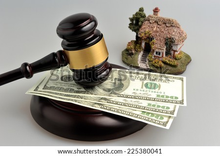 Gavel of judge with dollars and model of house on gray background - stock photo