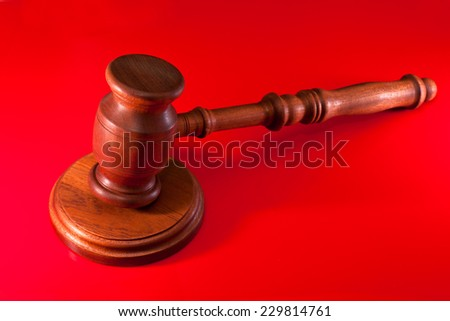 Gavel on red background - stock photo