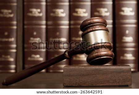 Gavel on wooden desk with books as background - stock photo