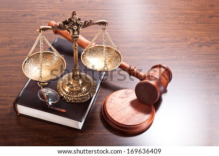 Gavel, scales, glasses and a book on the table - stock photo