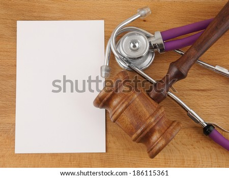 Gavel, stethoscope and blank paper on wooden background - stock photo