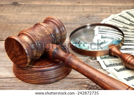 Gavel, USA Dollars and Vintage Magnifying Glass on Grunge Wood Table - stock photo