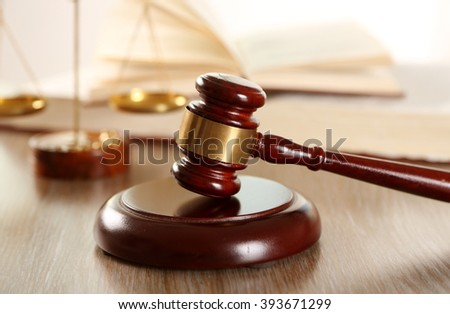 Gavel with books and scales of justice on wooden table closeup