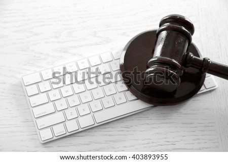 Gavel with computer keyboard on wooden table closeup - stock photo