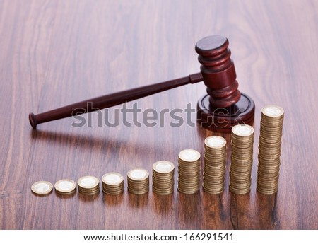 Gavel With Pile Of Coins On Wooden Desk - stock photo