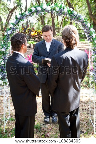 Gay couple being married by their minister outdoors under a floral archway. - stock photo