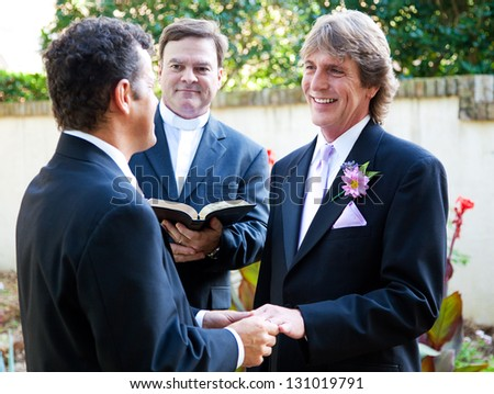 Gay couple exchanging rings and vows at their wedding. - stock photo