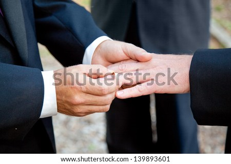 Gay couple exchanging rings at their wedding ceremony - stock photo