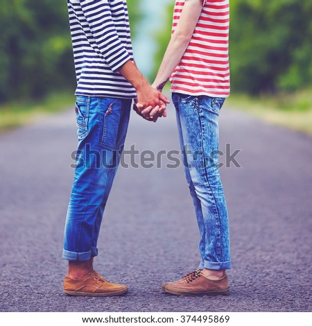 gay couple holding hands together on spring road