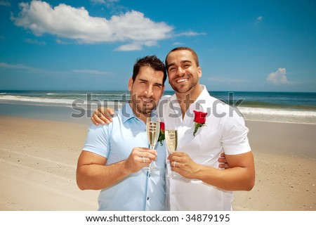 Gay couple on a beach after getting married - stock photo