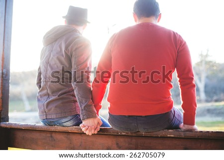 Gay couple sitting in a meadow enjoying the view - stock photo