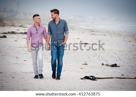 gay couple taking a walk along the beach holding hands - stock photo