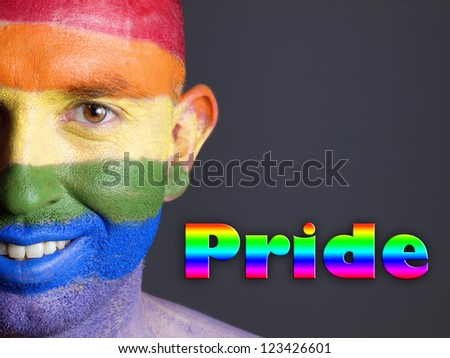"""Gay flag painted on the face of a man. Man is looking at camera and is smiling. The word """"pride"""" is writte at one side. - stock photo"""