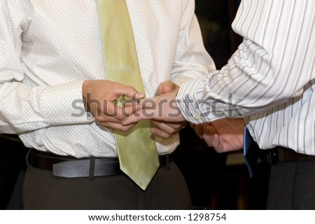 gay husband puts ring on spouse 's finger - stock photo
