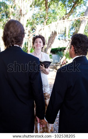 Gay male couple getting married by a female minister. - stock photo