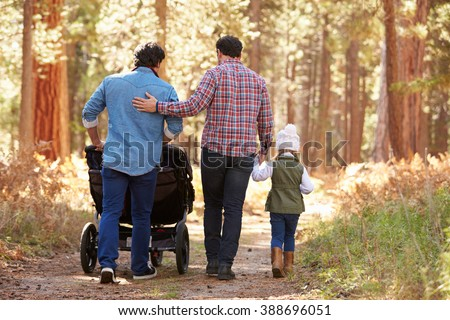 Gay Male Couple Pushing Children In Buggy Through Woods - stock photo
