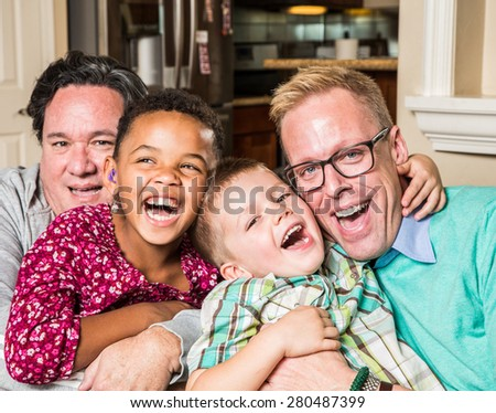 Gay parents and their children pose for a photo at home - stock photo