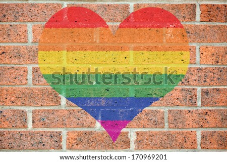 Gay pride colored heart shape painted on old red brick wall - stock photo