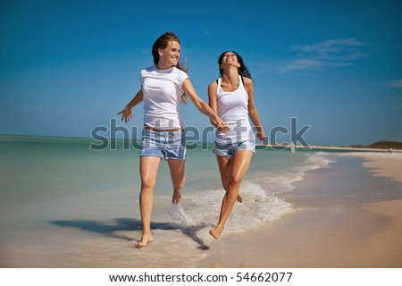 Gay women running at the beach