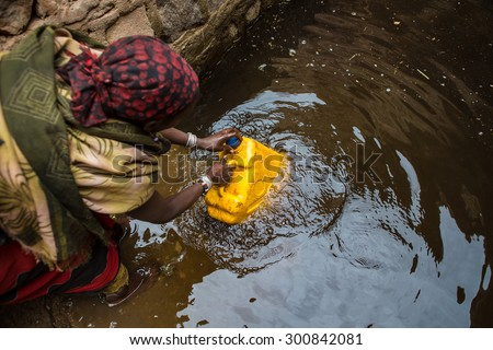 GAYO VILLAGE, ETHIOPIA - JUNE 19: Woman takes water from a well before returning to her village. The water is purified with tablets before drinking on June 19, 2012 in Gayo village, Ethiopia.   - stock photo