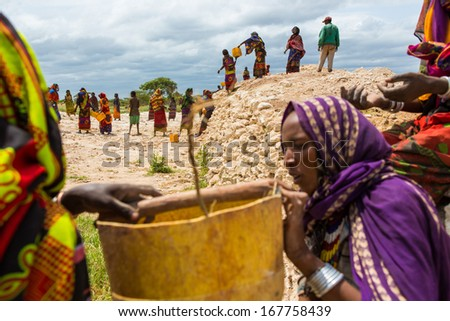 GAYO VILLAGE, ETHIOPIA - JUNE 19: Women work on building a well which is used by the people and animals as the only water source nearby on June 19, 2012 in Gayo village, Ethiopia. - stock photo
