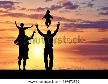 Gays and family. Pair of gay men and their children playing at sunset on the sea
