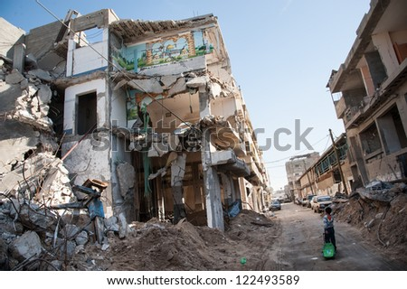 GAZA, PALESTINIAN TERRITORY - DECEMBER 2: A child passes a bombed-out residential block in the Al-Zeitoun neighborhood of Gaza City, December 2, 2012. - stock photo