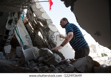 GAZA, PALESTINIAN TERRITORY - DECEMBER 3: A government employee searches for documents amid the rubble of the Palestinian National Authority Council of Ministers building, December 3, 2012. - stock photo